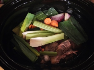 [ID: shiny black oval slowcooker pot, looked at from above, with various vegetables (carrot tops, a quartered onion, crushed garlic, celery sticks, leek trimmings) and leftover chicken bones visible in water]